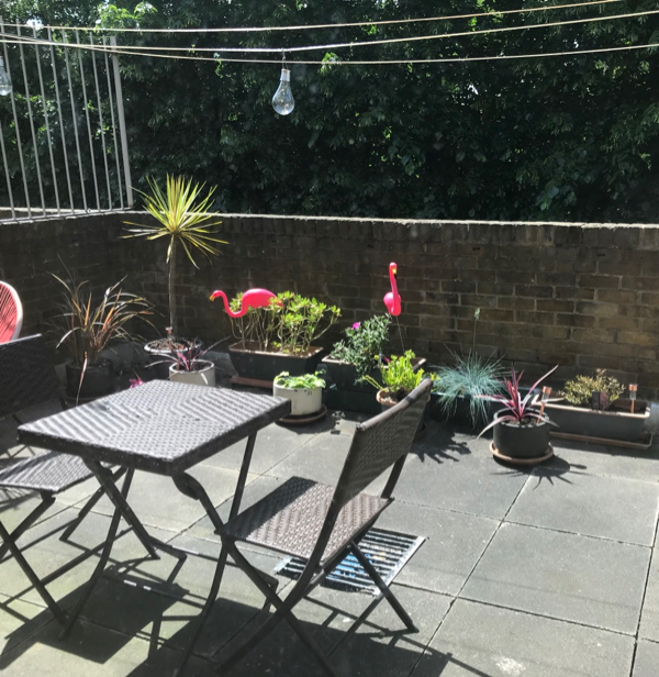 Patio with pots of plants and pink flamingos